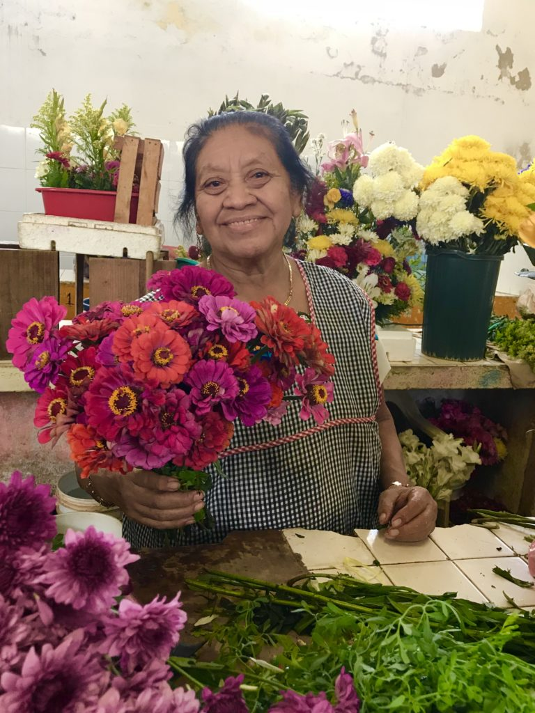 Mercado Santiago Visit with the local flower lady who has red flowers living in Mérida.