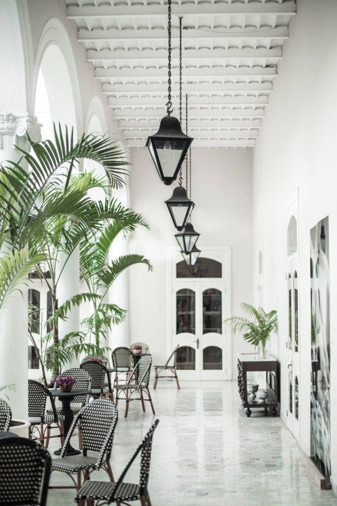 Casa Tho in Mérida. A great place for this living in Merida. A shop filled with local artists where there is a beautiful white courtyard outside with plants, white walls, and light fixtures to eat and drink coffee.