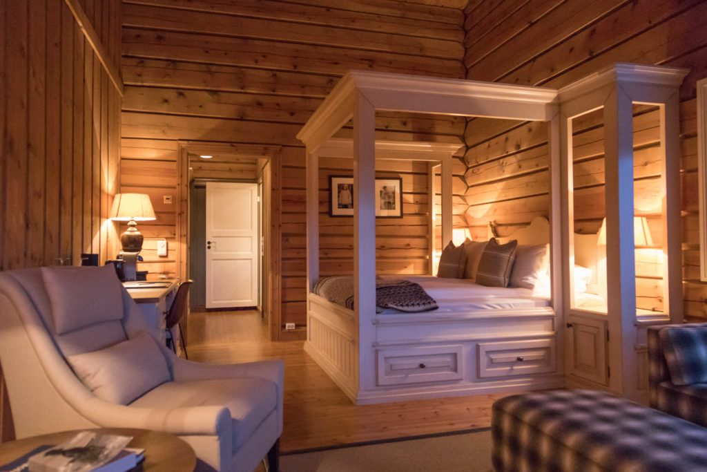 Storfjord Hotel suite room in Norway with couch, bed and minibar.
