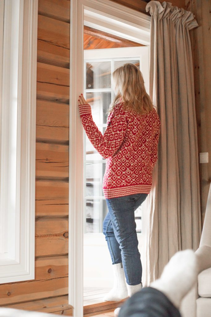 Storfjord Hotel suite room with girl looking out door to beautiful views of Norway.