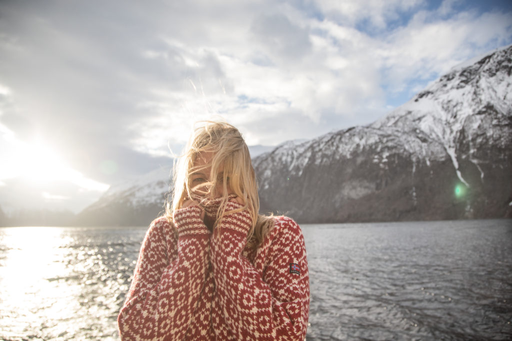Girl in Norway fjord wearing Devold sweater in winter.
