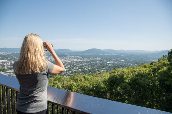 Blonde girl with binoculars looking out on Roanoke Valley in Virginia's Blue Ridge