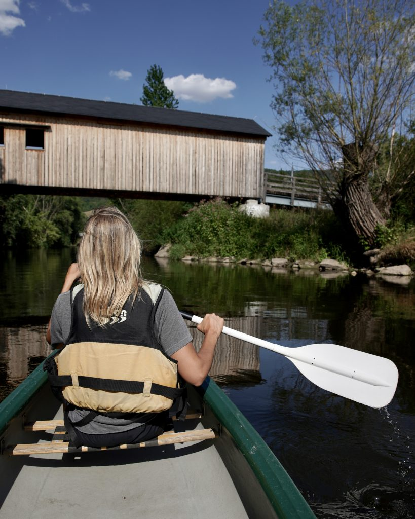 blonde woman canoeing down river