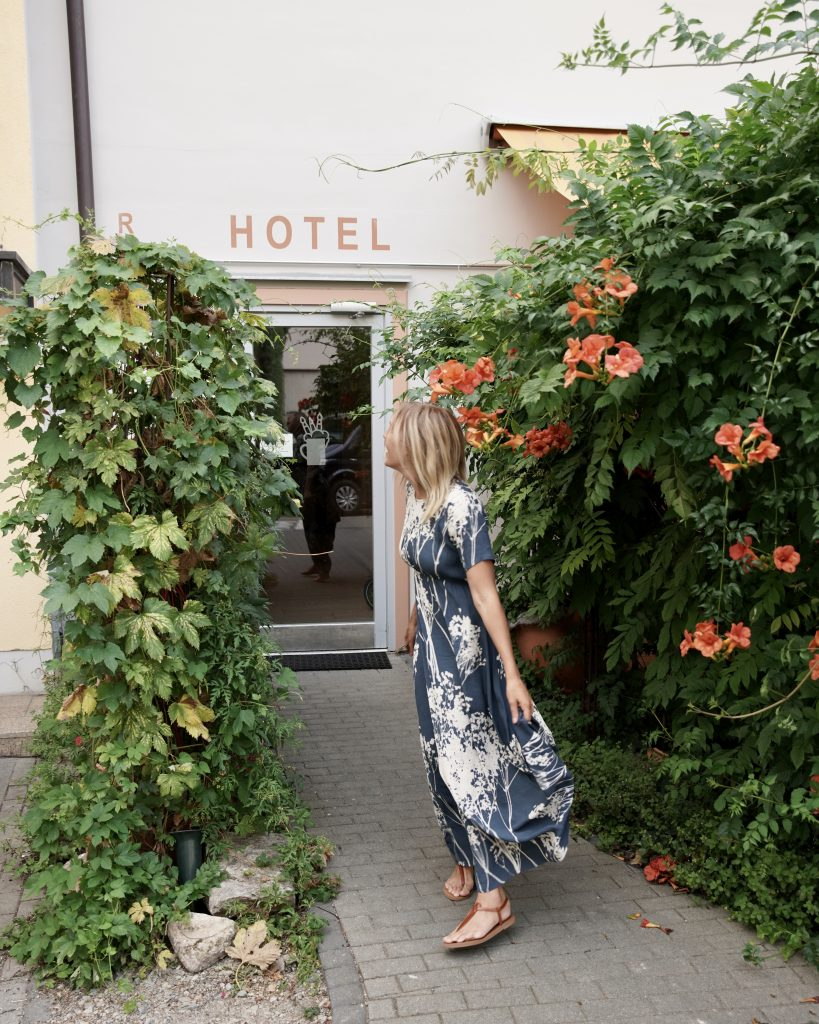 Blonde gril in long dress in front of flowers and hotel sign