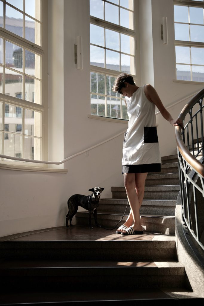 dark hair woman and dog walking in spiral staircase